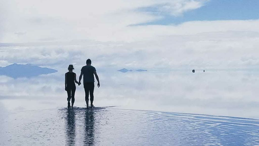couple enjoy the surreal view at uyuni salt flats desert in bolivia south america
