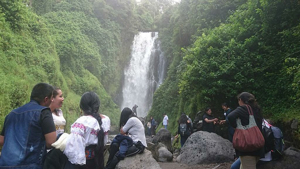 locals in indigenous dress sitting on rocks at peguche waterfall otavalo ecuador