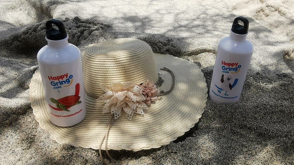 happy gringo water bottles and straw hat on the sand