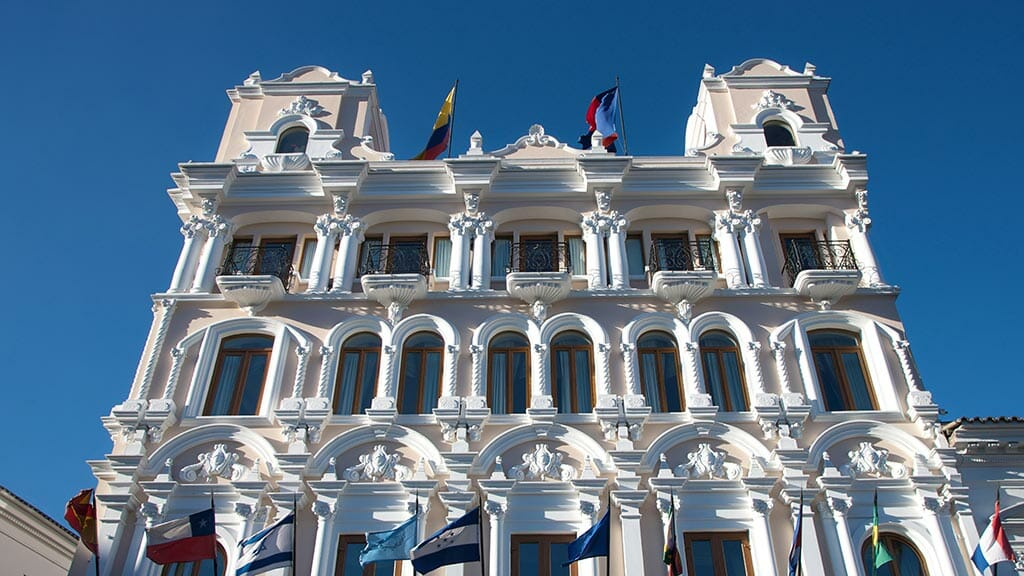 attractive pink and white fachade of colonial style hotel plaza grande quito ecuador