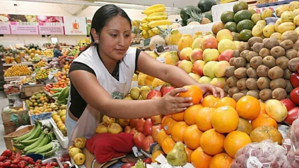woman selling colorful fruits at santa clara market quito ecuador