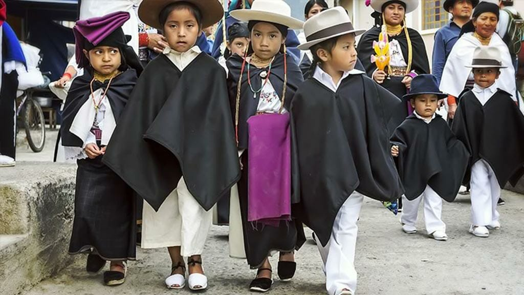 children dressed in ponchos and hats for pawkar raymi festival in ecuador