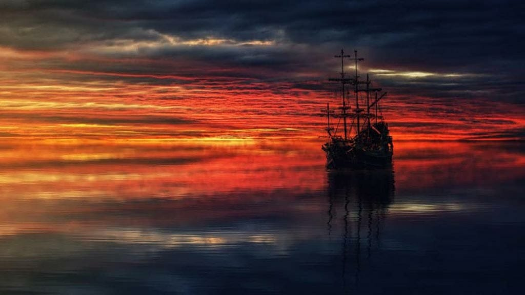 galapagos sunset with silhouette of old sailing ship