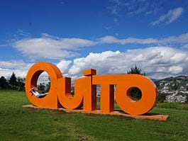 tourist relaxes against big quito tourism sign metropolitan park