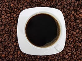ecuador coffee - a cup of black coffee on top of a table of coffee beans