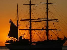 galapagos islands traditions - a lareg sailing ship crossing the equator at sunset