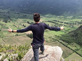 tourist with arms stretched out admiring amazong view of green andes mountains