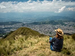 tourist sitting on rucu pichincha volcano with view of quito city