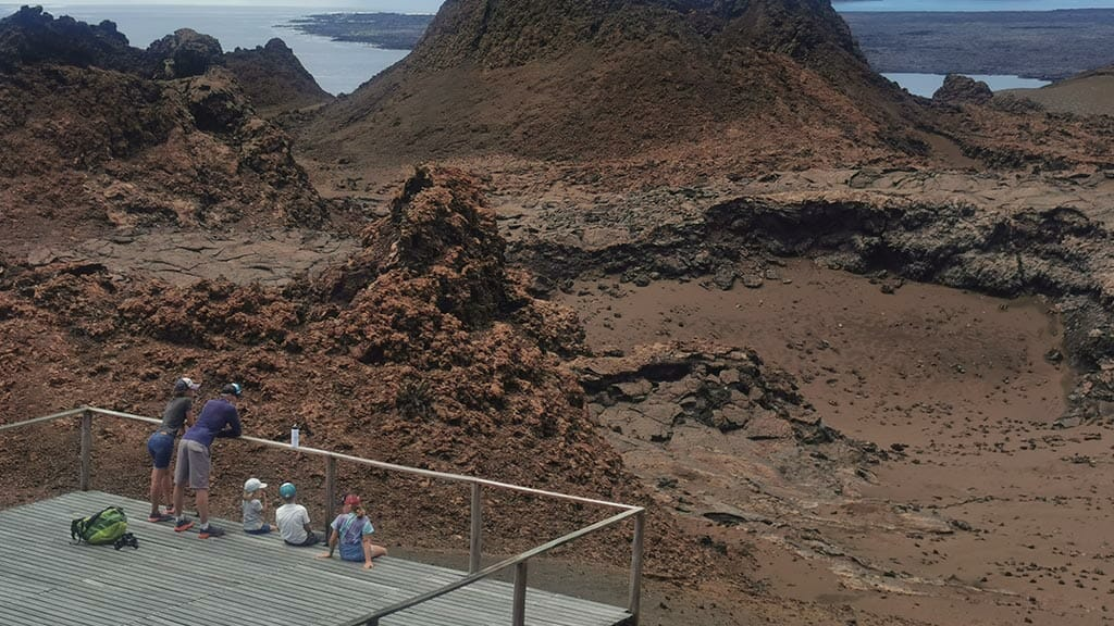 family enjoy moon like lava landscape at bartolome galapagos