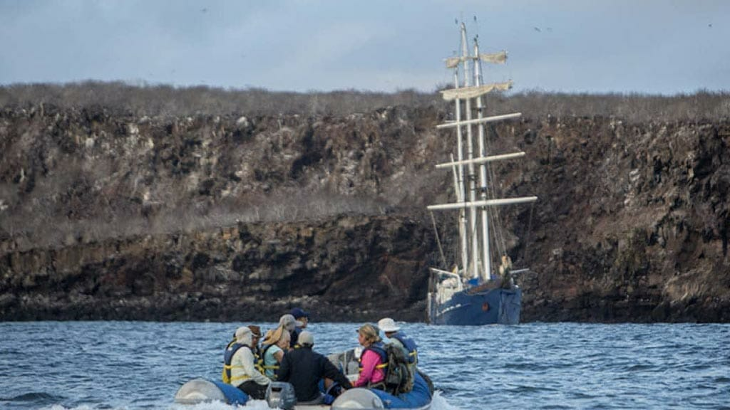 tourists return to the mary anne yacht at the galapagos islands cruise