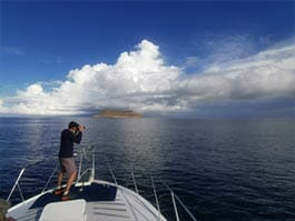 tourists taking a photo of daphne major island at the galapagos islands