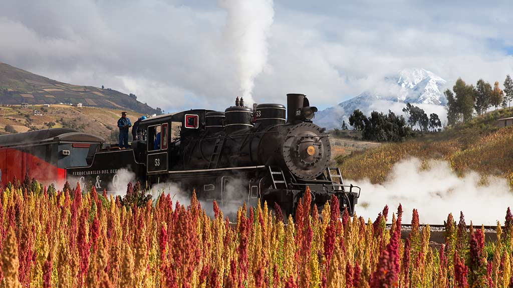 steam train in ecuador past crop fields and snow capped volcanos