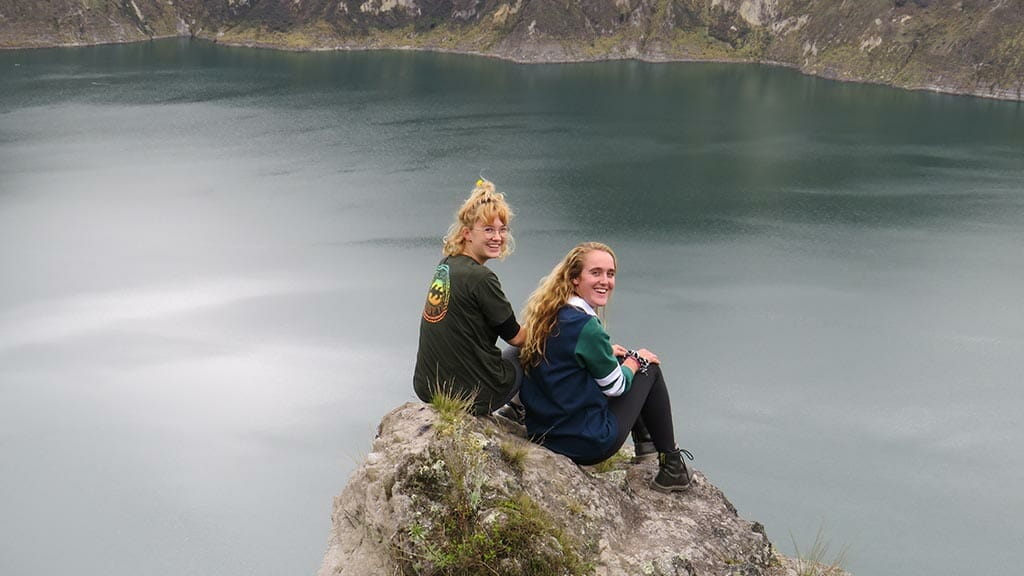 two female tourists pose on a rock in front of quilotoa lagoon ecuador