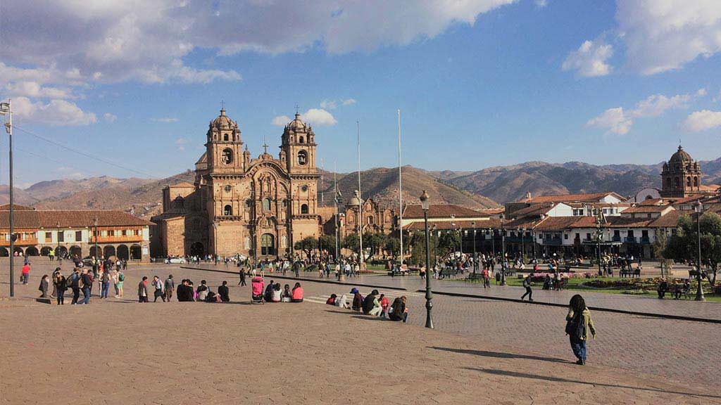 View of Cusco plaza in Peru full of people with cathedral in background