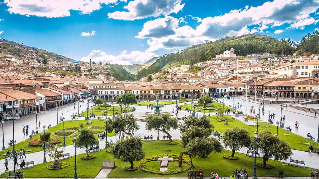central plaza of cusco peru with mountains and red roofs