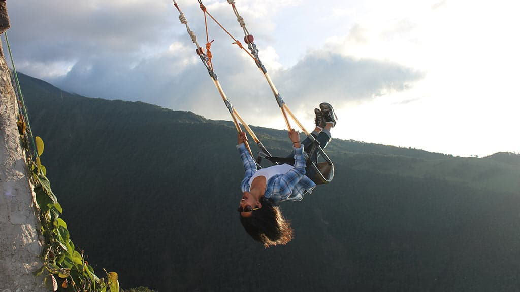 girl upside down on the swing at the end of the world baños ecuador