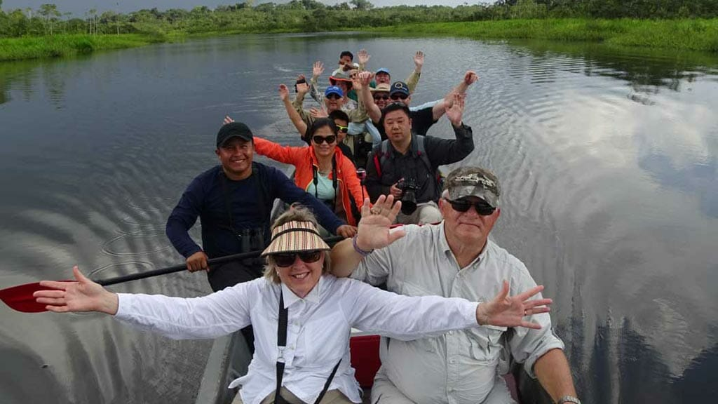 Tourists aboard canoe in Amazon Rainforest in ecuador