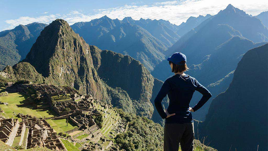 A tourist looks out over the spectacular inca ruins of machu picchu peru with mountain background