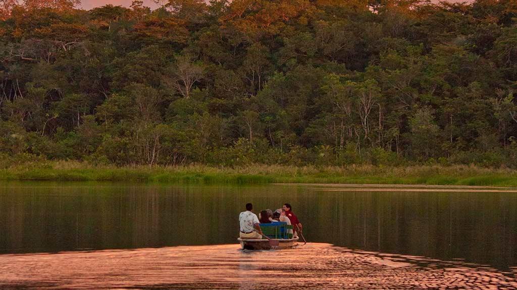 guide and tourists canoe on the napo wildlife center lake in ecuador amazon