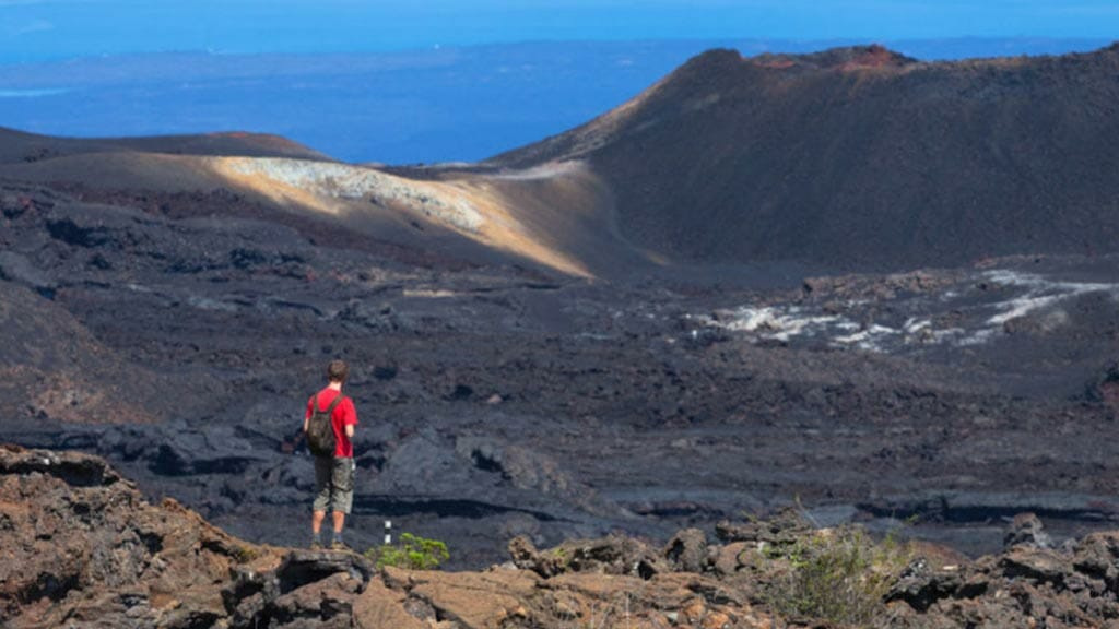galapagos islands volcanoes with tourist in red top