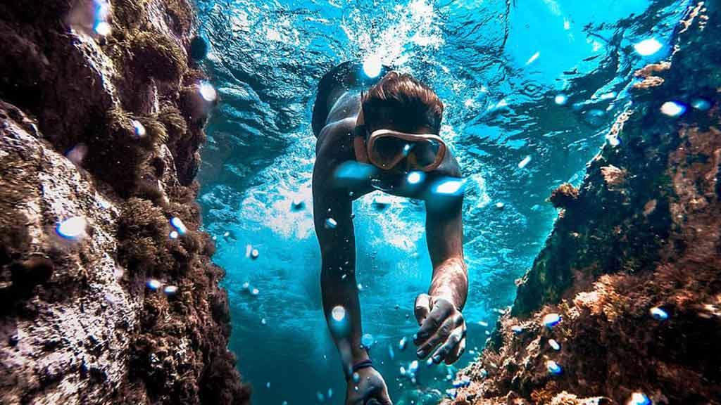 galapagos snorkeling: a snorkeler explores between the rocks