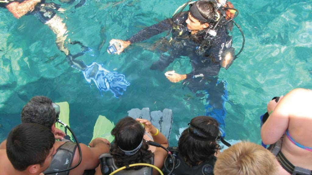 Galapagos guide gives a snorkeling safety demonstration to group of tourists