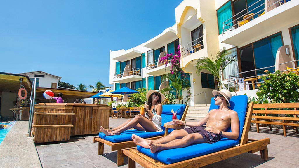Hotel sol y mar puerto ayora galapagos - tourists sunbathing by the pool