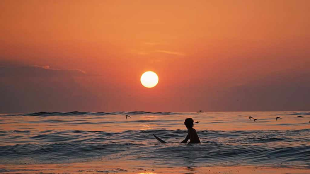 surfing at sunset on ecuador beaches