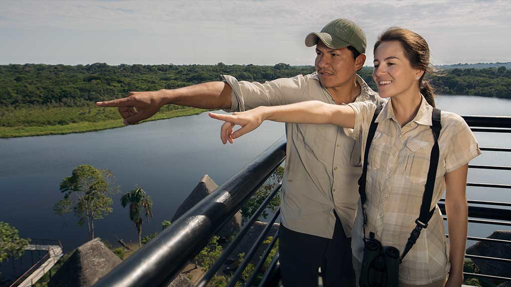 tourist couple on top of the napo wildlife center observation tower ecuador